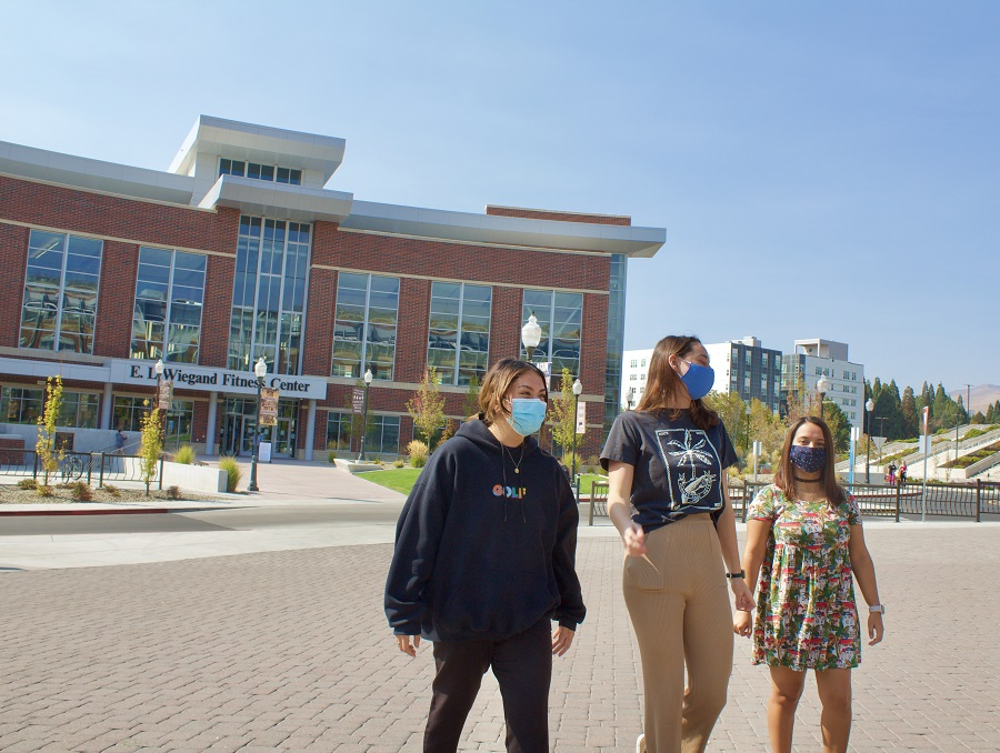 Students wearing face masks walking in front of the fitness center