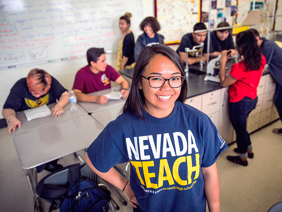 Nevada Teach student smiling with students in the background working on science project
