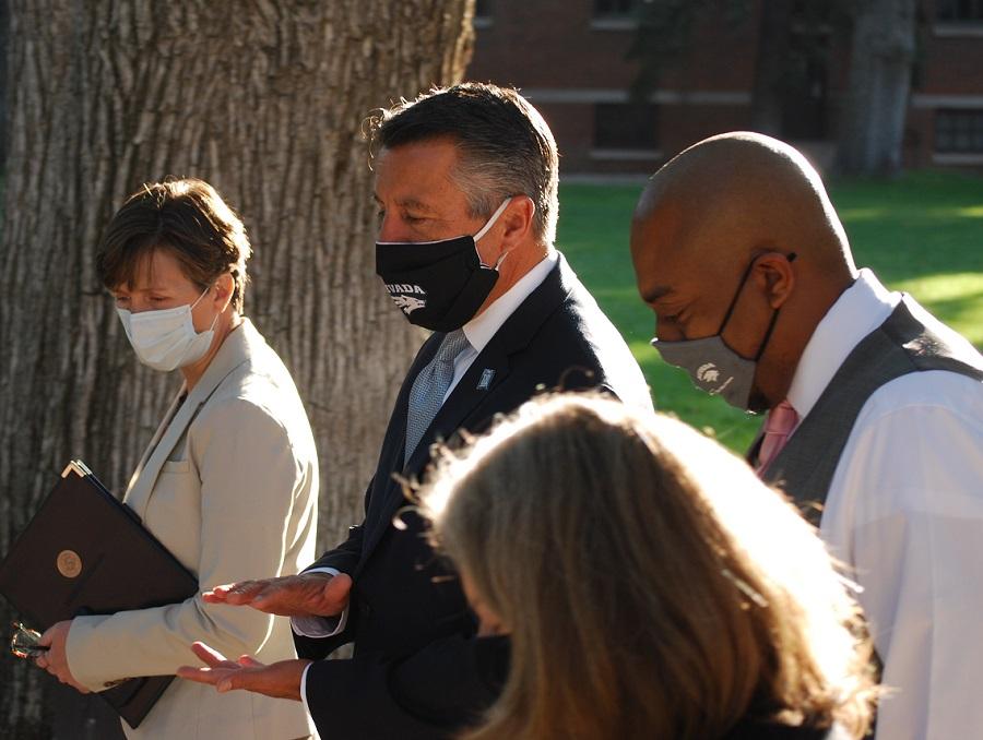 President Sandoval talks with senior administrators while walking on the quad