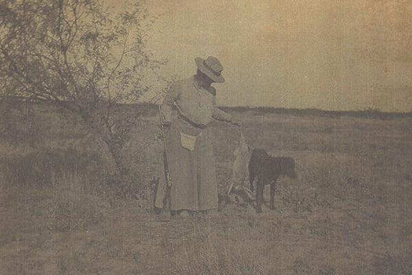 Scanned image of a woman holding a rifle and standing next to a black dog.