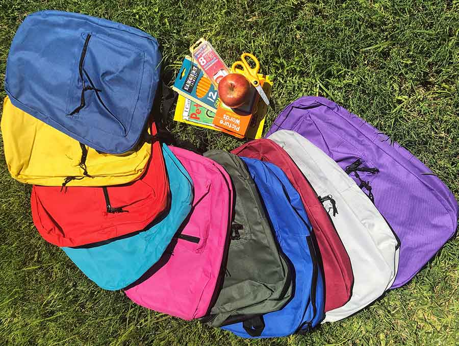 Backpacks of different colors with school supplies