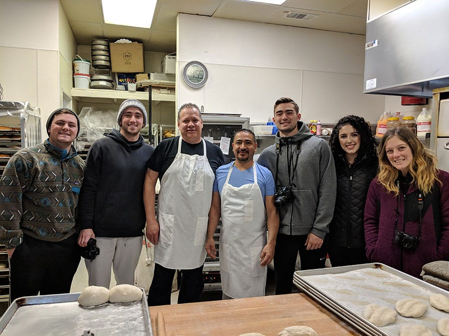 Students pose with local Latino bakers inside a bakery in northern Nevada.