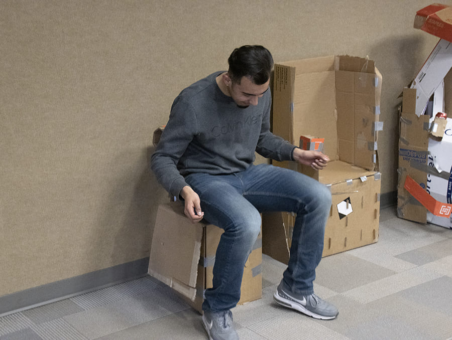 student sitting on cardboard chair