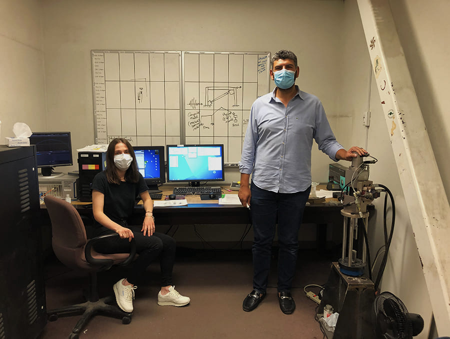 Two people in small lab with computer
