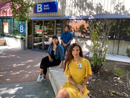 Nevada Public Health Training Center disease investigators Dulce Leyva, Cynthia Cabrales, seated, and Luis Godoy, standing, in a shaded courtyard at the Washoe County District Health facility in Reno.