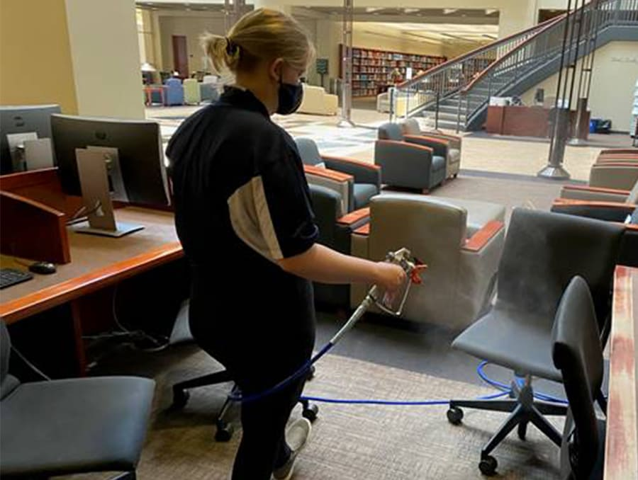 A Libraries Building Monitor uses OPIE to clean chairs inside the Mathewson-IGT Knowledge Center.
