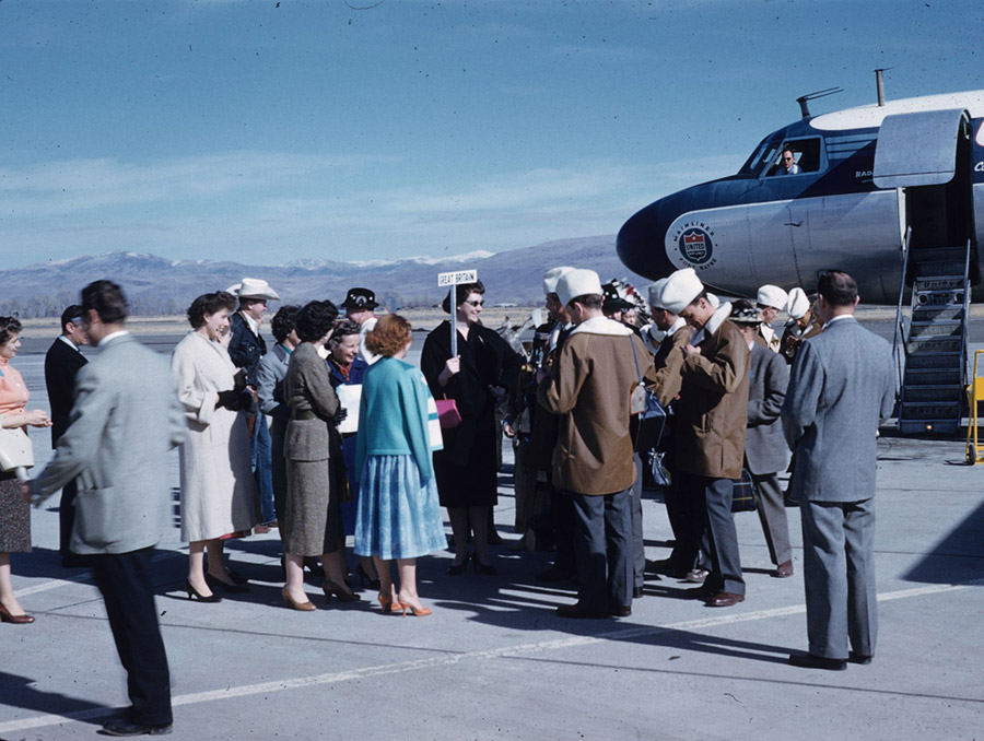 "A color photograph showing a crowd standing on the tarmac at the Reno Tahoe Airport. A woman holds a sign with ""Great Britain"" on it, while a group of people wearing matching brown coats with white hats stand near her. A United Airlines airplane is in the background with a stairway down to the tarmac."