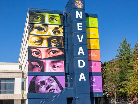 Sierra Hall mural featuring six sets of diverse eyes and faces with Nevada painted down the column
