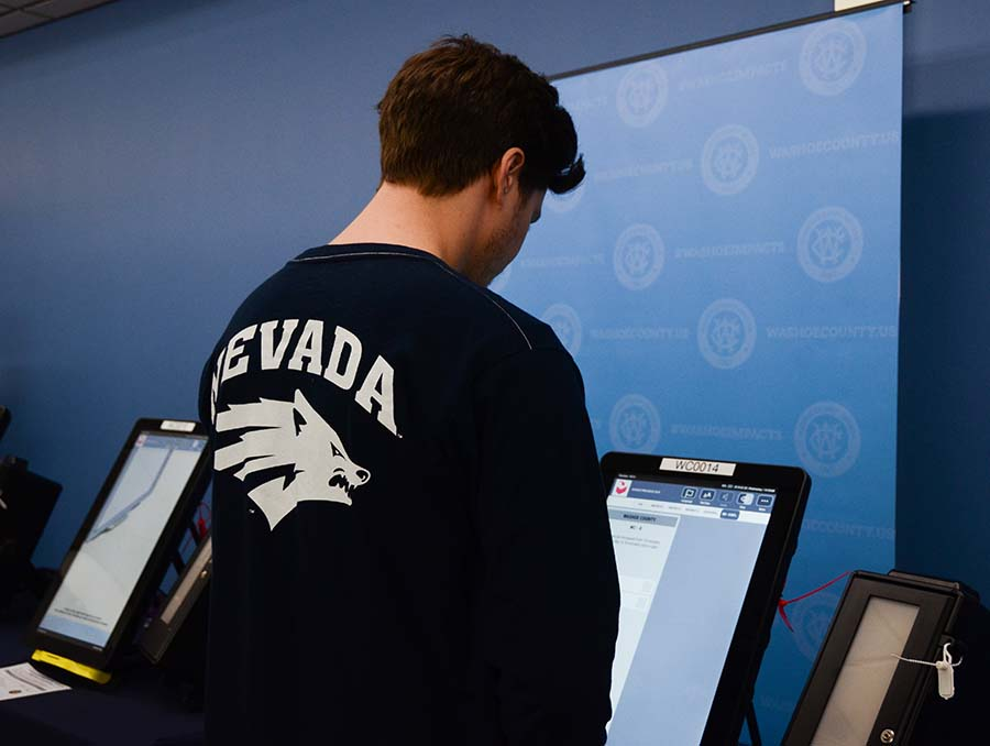 Person with a Nevada Wolf Pack shirt on stands in front of a voting machine.