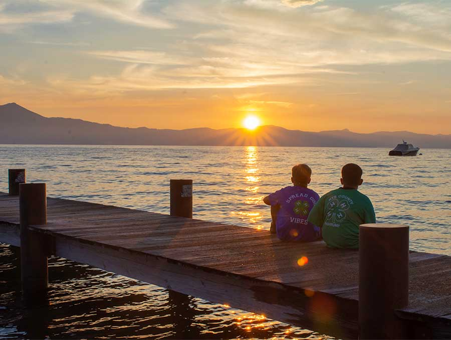 4-H'ers sitting on the dock at 4-H Camp in Lake Tahoe, enjoying the sunset.