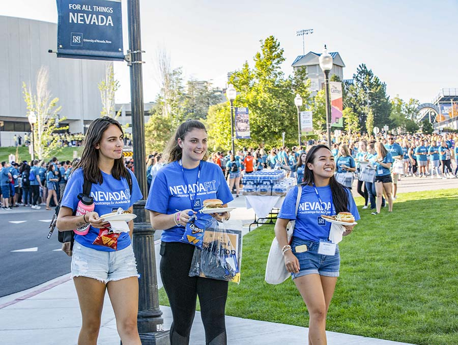 Students in blue shirts with food plates in hand walk through the Gateway plaza on the University of Nevada, Reno campus.