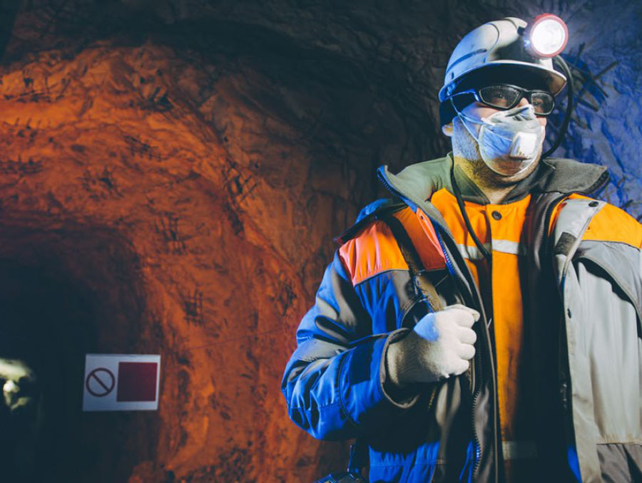 Man in an underground mine wears a face covering.