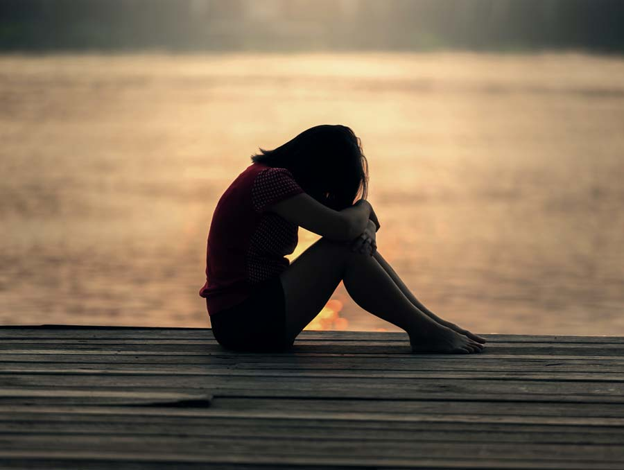 Silhouette of girl on a dock resting her forehead on her knees.
