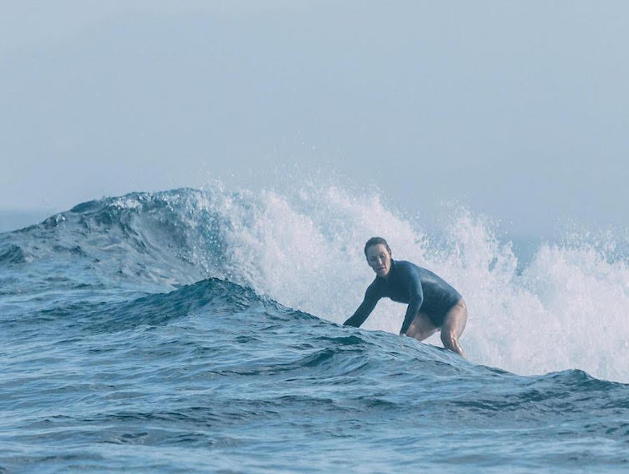 Heather Ernst surfing in the ocean.