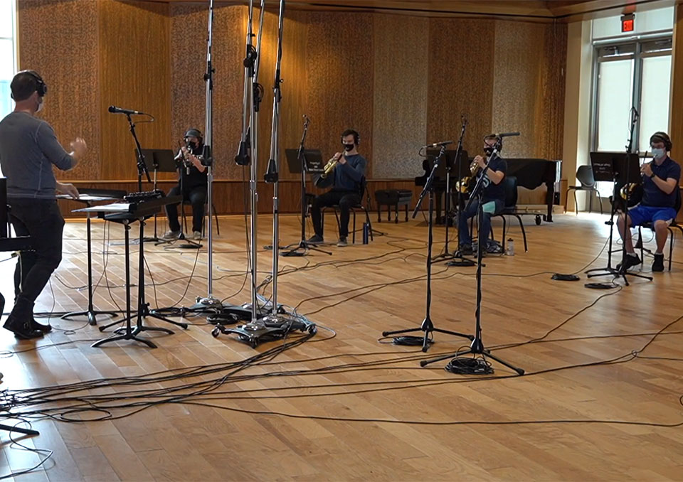 Student musicians sit socially-distanced in band room and record song with conductor