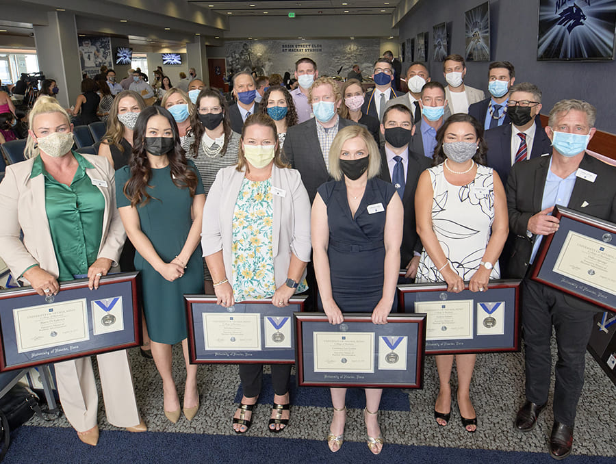The 2021 Online Executive MBA graduating class posing for a group photo while holding their degrees.