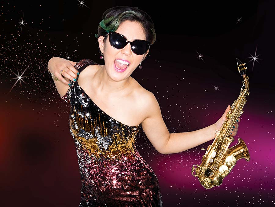 Performer Grace Kelly holds a saxophone.