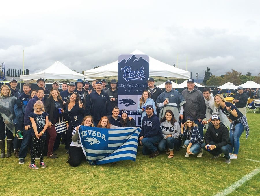 A group of people from the Bay Area Alumni Chapter wearing silver and blue Wolf Pack gear