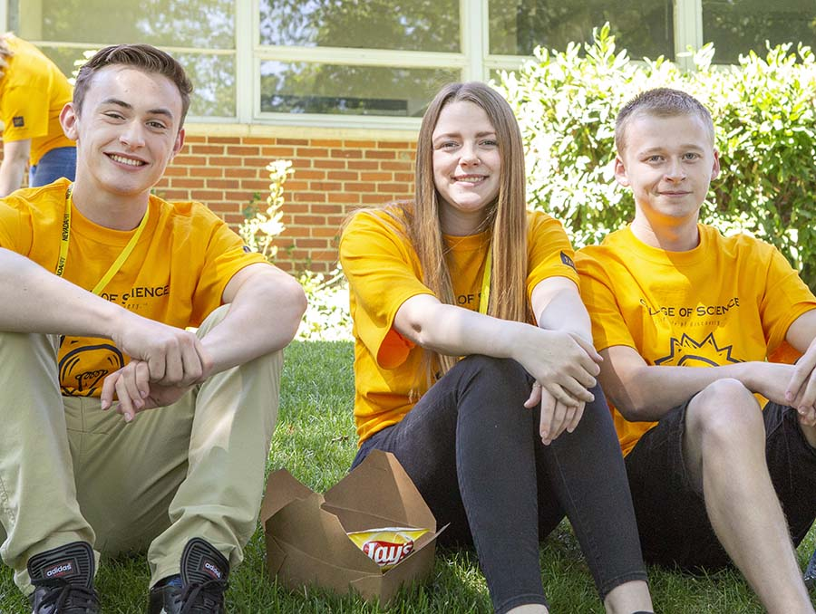 Students sit on a grass hill with yellow shirts during an event on the University of Nevada, Reno campus.