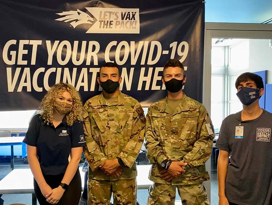 """Four people in masks stand in front of a banner reading, """"Get your COVID-19 vaccination here."""""""
