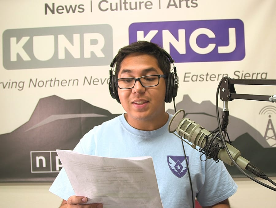 Andrew Mendez records voiceover in an audio studio at KUNR.