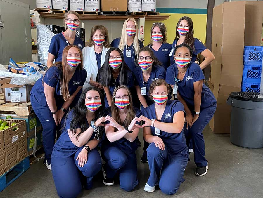 A group of nursing students wearing blue Orvis School of Nursing scrubs and masks
