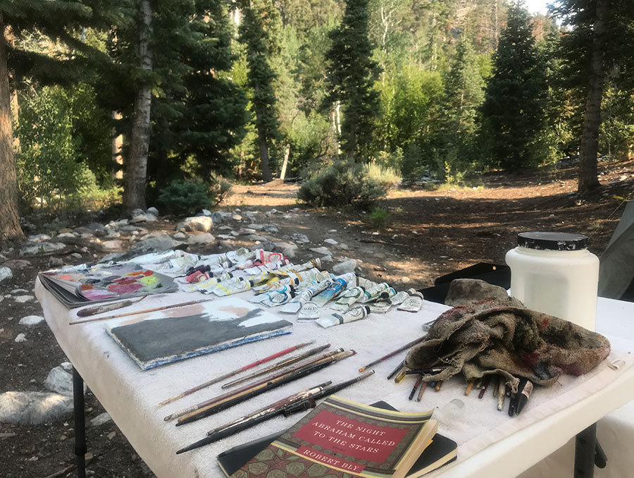Artist table with paint, brushes and canvas outside in campground