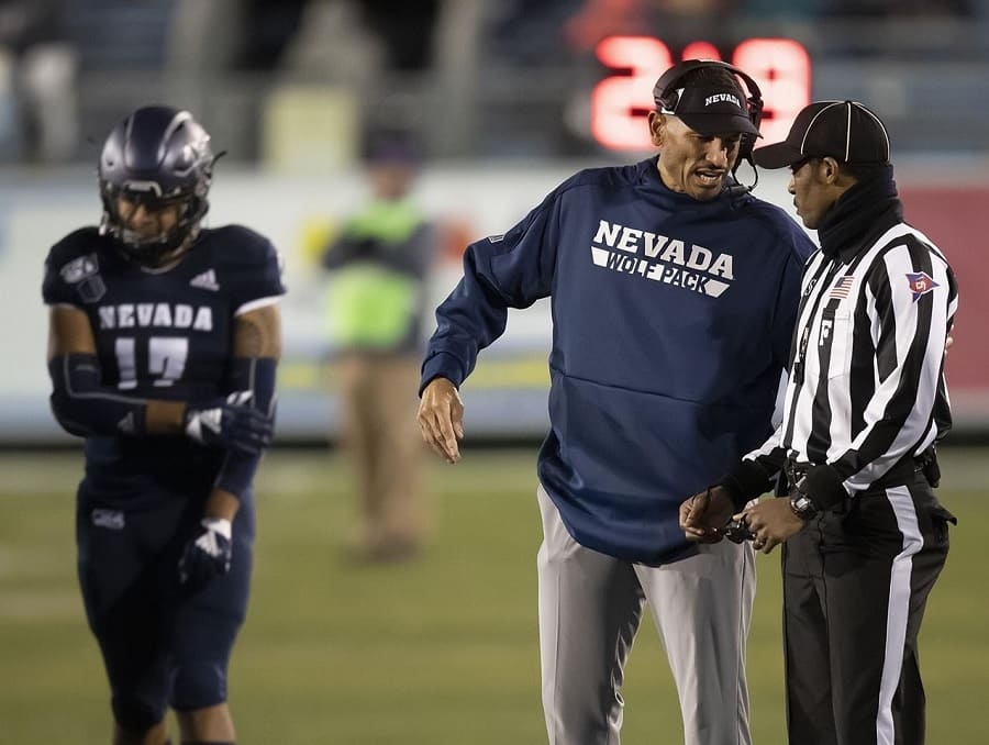 Coach Jay Norvell talking to a referee at Wolf Pack football game, a player and a game official can be seen in the background