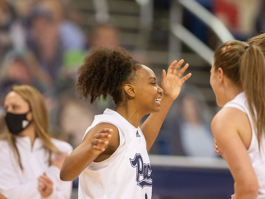 Nevada Wolf Pack Women's Basketball players celebrating on the court with a crowd visible in the background