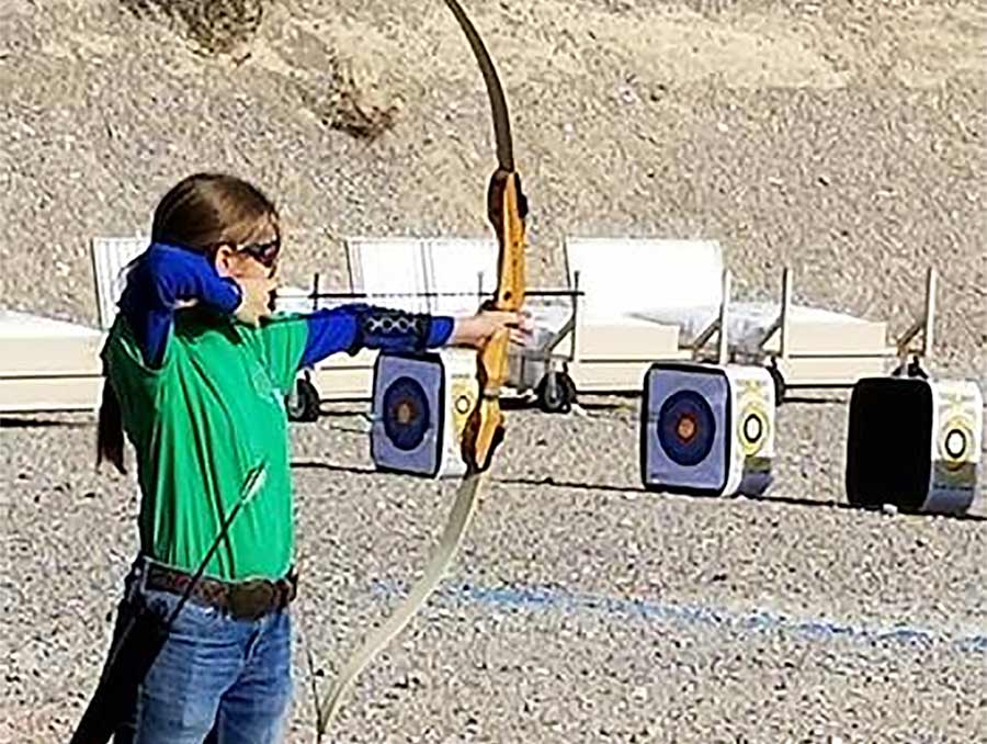 4-H youth shooting targets with a bow and arrow