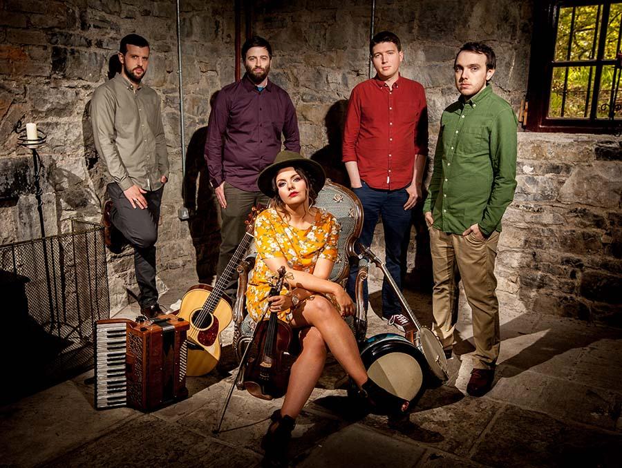 Irish quintet Goitse poses for a photo inside a brick room.