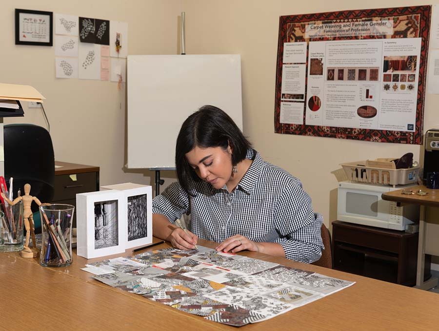 MFA student Sogand Tabatabaei sits at a desk working on a drawing.