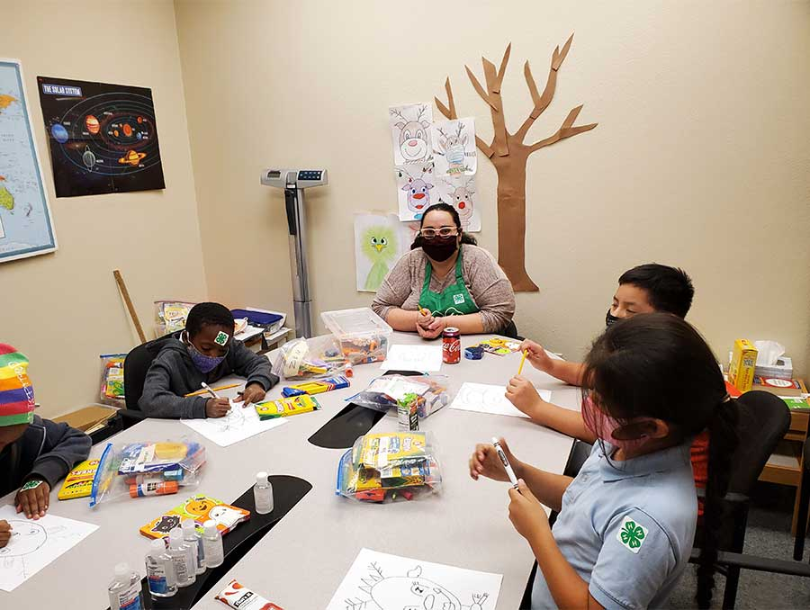 Samantha Shoupe and 4-H youth sit around a long rectangular table covered in craft supplies as they each draw reindeer. Educational posters (including one of the solar system) and kids' artwork adorn the walls.