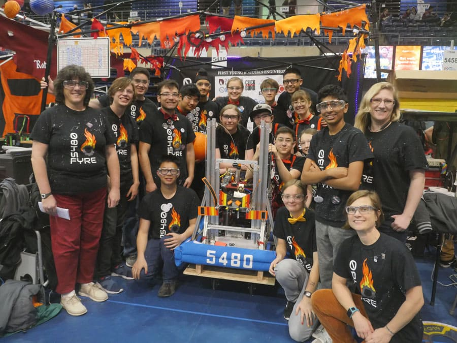 Kerry Thompson and her team of students stand around the robot they built at a competition.