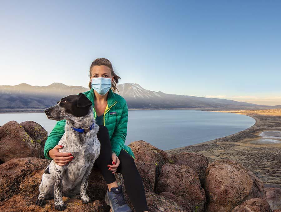 Assistant professor Kyra Stull with her dog Ozymandias sitting on rocks overlooking Washoe Valley Lake