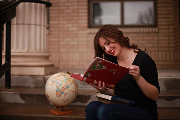 Young woman sitting and reading a book with a red cover.