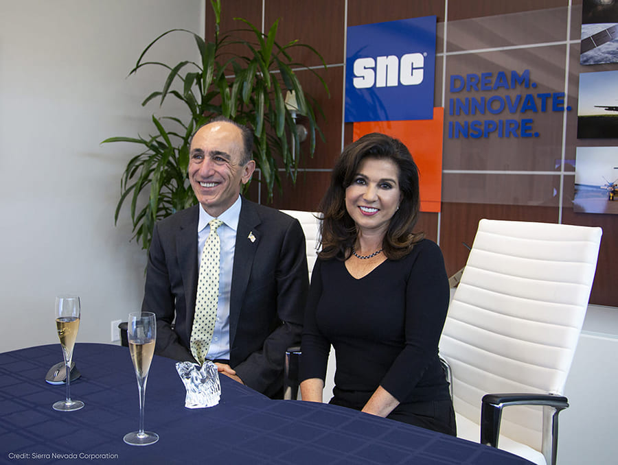 Two people seated at table with SNC banner in background