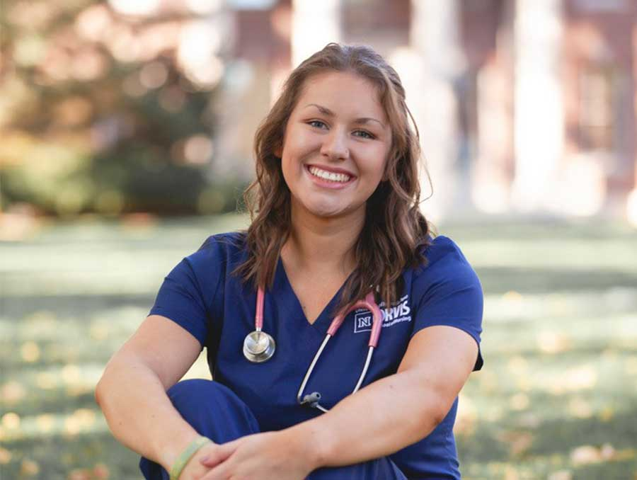 Haley Carroll sit in grass with nursing student uniform on