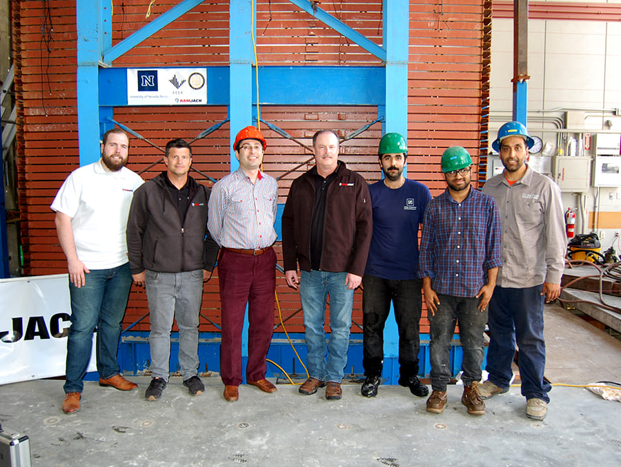 Seven researchers in front of soil box experimental structure