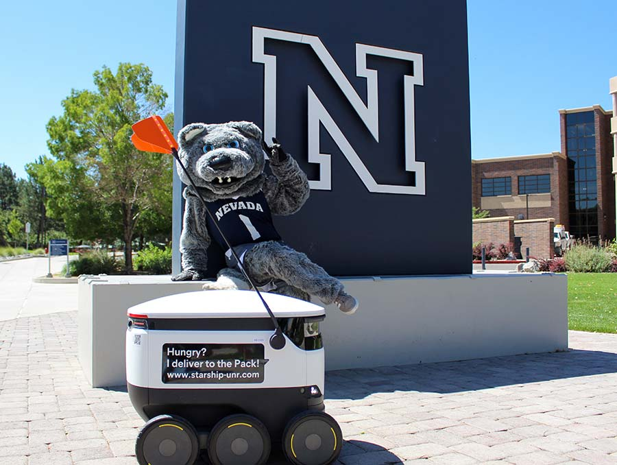 University of Nevada, Reno mascot Wolfie sits on the campus' N statue with a Starship food delivery robot at his feet