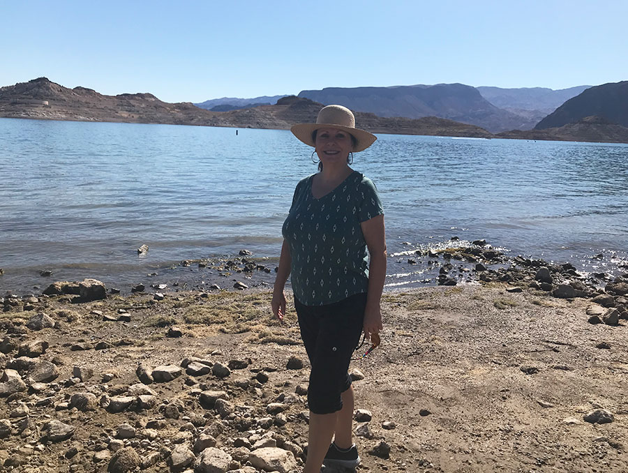 Eugenia Weiss standing by a lake wearing a green shirt, black leggings and a hat