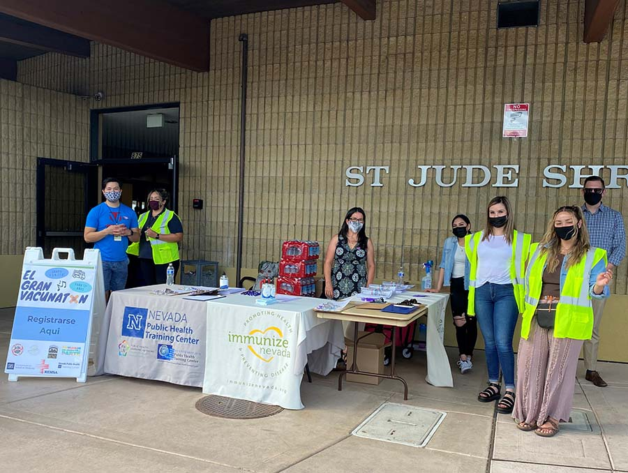 People stand around tables outside St. Therese of the Little Flower in Reno during a COVID-19 vaccination clinic