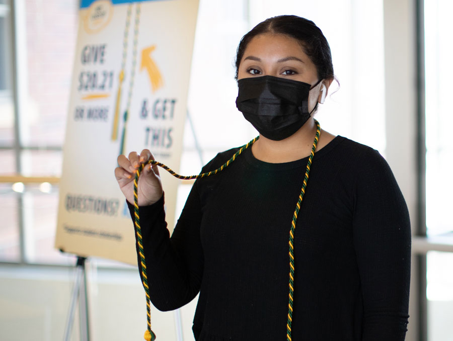 A student wearing a mask holds up a gold and green graduation tassel which hangs around her neck.