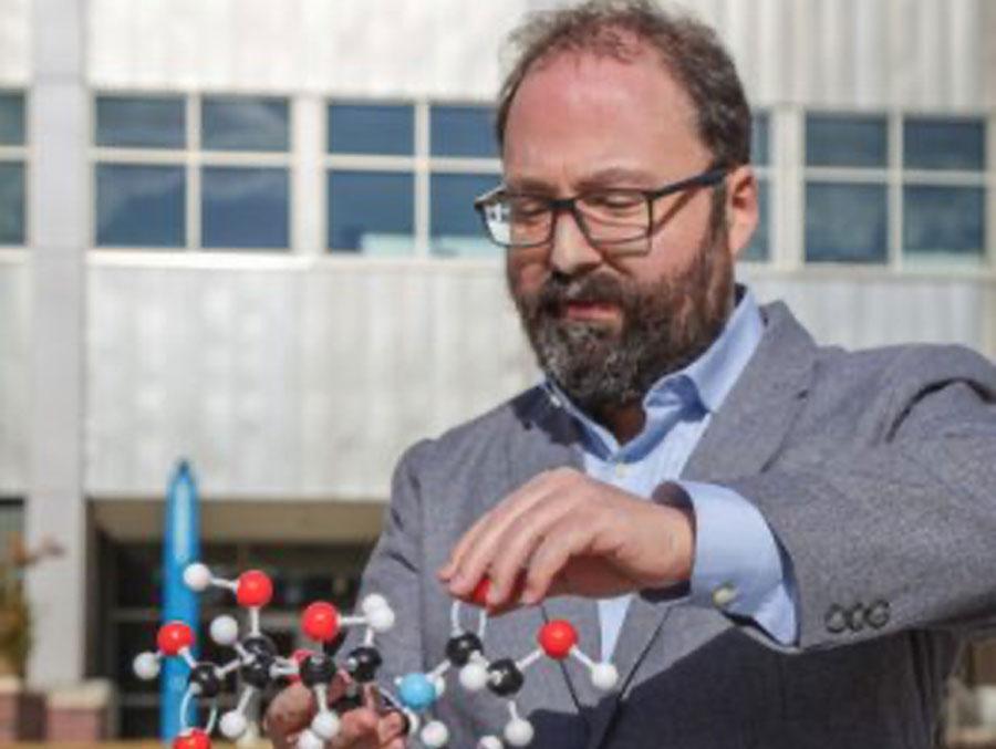 Assistant Professor in the Department of Biology David Alvarez Ponce holds a molecule model.