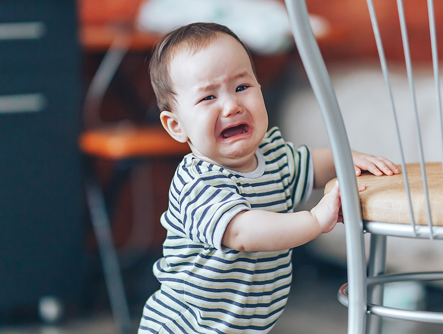 Crying child holding on to a chair