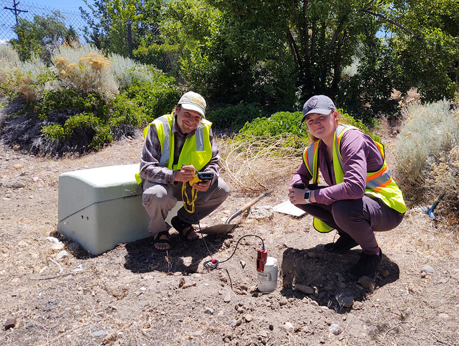 two researchers installing seismometer in ground