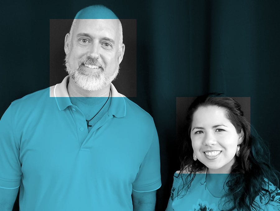 A man and a woman post on a black backdrop. The image is gray scale with a blue filter over the top. The filter is removed on both of the faces of the man and woman.