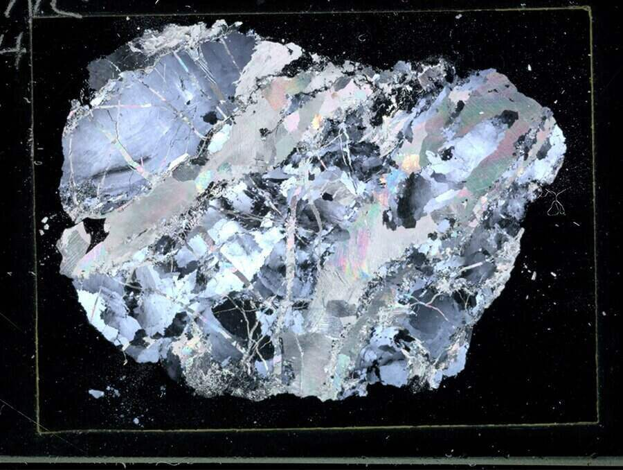 Thin section of brecciated quartz appears on a black background. Colors in the image appear as silvery, blue tones with flecks of black throughout