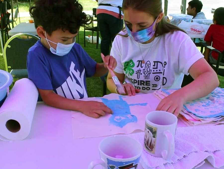 A 4-H youth works with a 4-H leader on a STEM project. See caption for more detail.