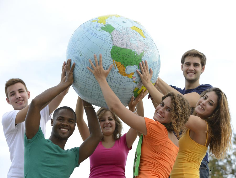 Diverse group of teenagers hold up an inflatable globe.